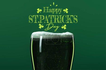 Photo pour Verre de bière avec mousse près heureux st patricks lettrage jour sur fond vert - image libre de droit