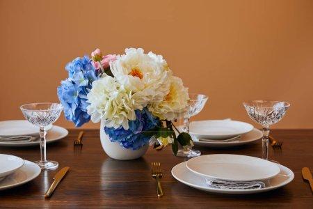 Foto de Placas de oro, cuchillos y tenedores, copas de cristal y bouquet en florero blanco sobre mesa de madera aislaron en beige - Imagen libre de derechos