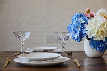 Photo pour Assiettes blanches, couteaux et fourchettes, verres en cristal et bouquet dans un vase sur une table en bois près d'un mur de briques à la maison - image libre de droit