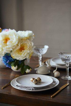 Foto de Enfoque selectivo de codorniz huevos en placas blancas, flores y copas de cristal en la mesa de madera en casa - Imagen libre de derechos