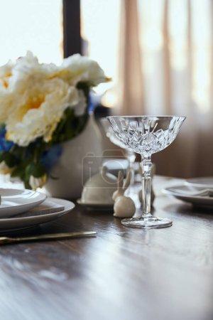 Foto de Enfoque selectivo del vidrio cristalino, bouquet en florero y bunnie decorativa sobre mesa de madera en casa - Imagen libre de derechos