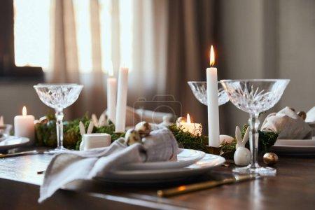 Foto de Enfoque selectivo de la quema de velas cerca de las placas y copas de cristal en la mesa de madera en casa - Imagen libre de derechos