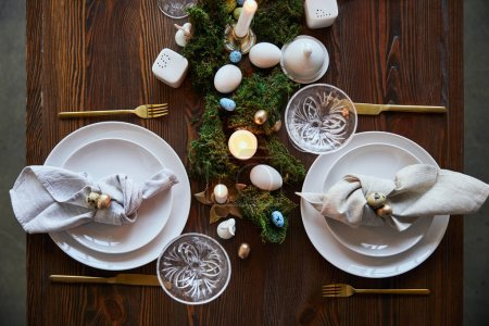 Photo for Top view of quail eggs on napkin and plates near green moss, candles and crystal glasses on wooden table - Royalty Free Image
