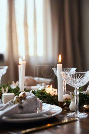 Foto de Enfoque selectivo de velas ardiendo cerca de las placas, vidrios cristal y musgo en mesa de madera en casa - Imagen libre de derechos