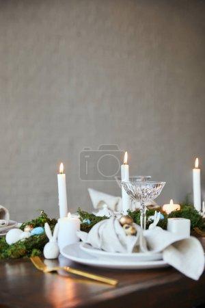 Foto de Enfoque selectivo de codorniz huevos en servilleta y placas verde musgo, velas y copas de cristal en la mesa de madera en casa - Imagen libre de derechos