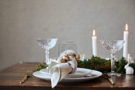 Foto de Enfoque selectivo de los huevos de codorniz sobre servilleta y placas, verde musgo, velas y copas de cristal en la mesa de madera en casa - Imagen libre de derechos