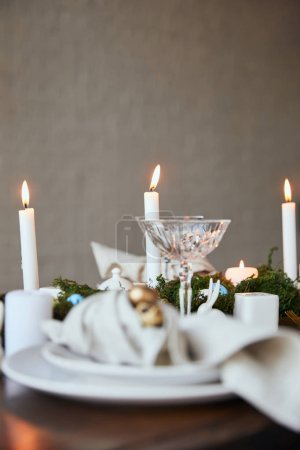 selective focus of candles and crystal glass on wooden table at home
