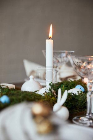 Photo for Selective focus of burning candles, crystal glasses and decorative bunnie on wooden table at home - Royalty Free Image