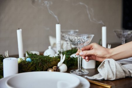 Photo for Cropped view of woman putting crystal glass near plates, candles and moss on wooden table at home - Royalty Free Image