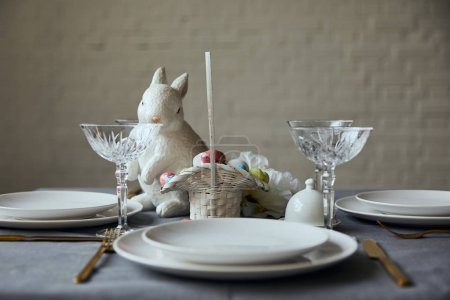 Photo for White plates, cutlery, crystal glasses, decorative bunnie and basket with painted eggs on table at home - Royalty Free Image