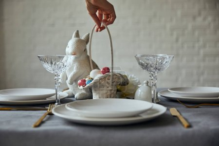 Photo for Cropped view of woman putting basket with painted eggs near white plates, crystal glasses and decorative bunnie on table at home - Royalty Free Image