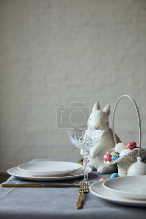 Foto de Placas blancas, cristal, decorativa bunnie y canasta con huevos pintados en la mesa en casa - Imagen libre de derechos