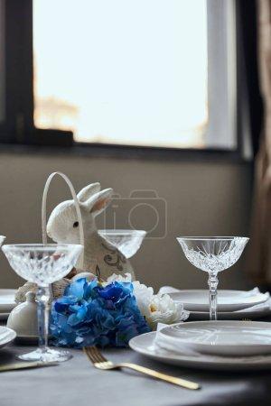 Foto de Placas, cristal, bunnie decorativo y flores en la mesa en casa - Imagen libre de derechos