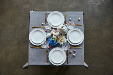 Photo for Top view of table with white plates, cutlery, crystal glasses, cutlery, painted eggs and flowers at home - Royalty Free Image