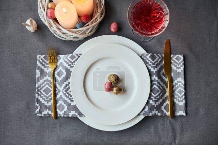 Photo pour Vue du dessus des assiettes avec serviette en tissu, oeufs et bougies allumées dans le panier, vin en verre de cristal sur la table à la maison - image libre de droit