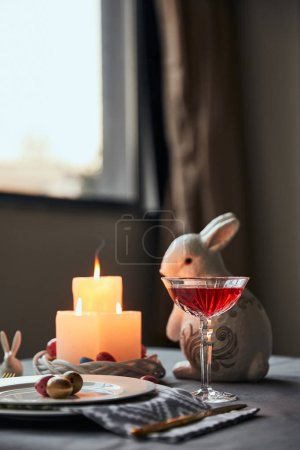 Photo for Selective focus of plates with eggs, wine in crystal glass and decorative rabbit  on table at home - Royalty Free Image