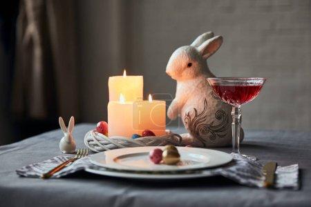 Foto de Enfoque selectivo de las placas con los huevos, el vinos en cristal, quema de velas y conejitos decorativos en la mesa en casa - Imagen libre de derechos