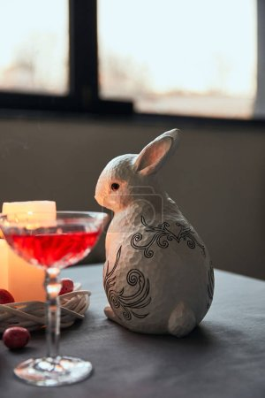 decorative bunnie, eggs, wine in crystal glass and burning candles on table at home