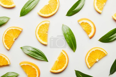 Photo for Top view of orange slices and green leaves on white background - Royalty Free Image