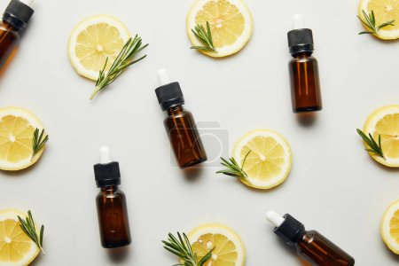 Photo for Flat lay with bottles of essential oil, lemon slices and rosemary on grey background - Royalty Free Image