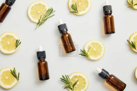 Photo for Flat lay with essential oil in bottles, lemon slices and rosemary on grey background - Royalty Free Image