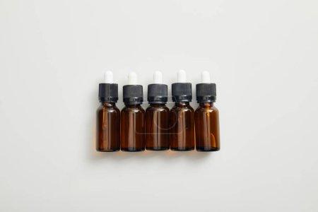 Photo pour Vue de dessus des bouteilles brunes avec huiles essentielles sur fond gris - image libre de droit