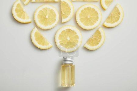 Photo pour Pose plate à l'huile essentielle et citron coupé sur fond gris - image libre de droit