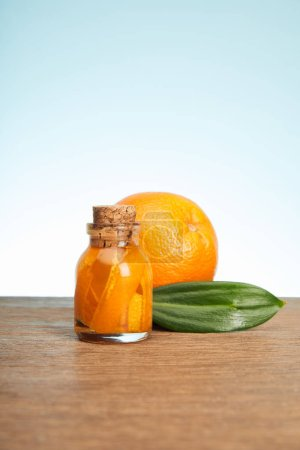 Photo pour Bouteille orange mûre et verre debout sur une surface en bois - image libre de droit