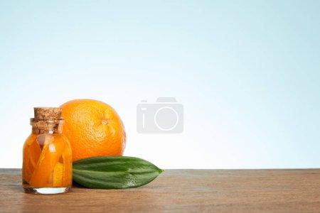 Photo pour Bouteille en verre et orange mûre avec une feuille verte sur la surface en bois - image libre de droit