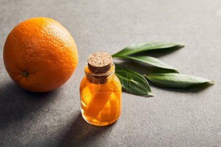 Foto de Naranja entera madura y botella con aceite esencial de superficie oscura - Imagen libre de derechos