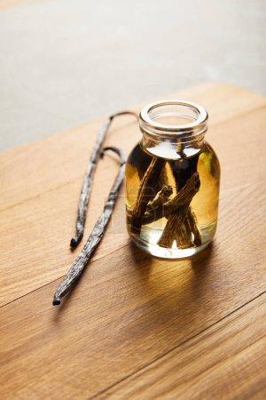 Photo pour Bouteille en verre d'huile essentielle avec gousses de vanille sur planche à découper en bois - image libre de droit