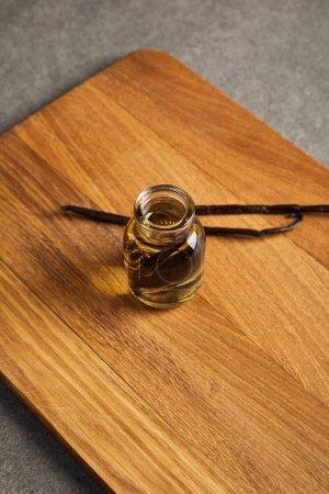 Photo pour Bouteille en verre d'huile essentielle avec des gousses de vanille sur une planche à découper en bois - image libre de droit