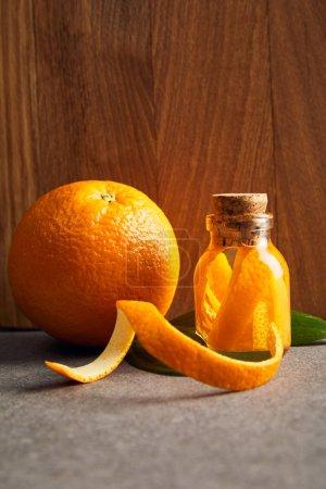 Photo pour Orange mûre et huile essentielle en flacon de verre sur fond en bois - image libre de droit