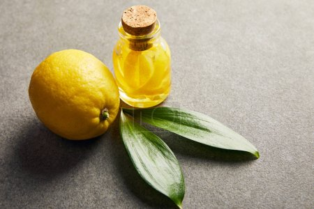 Photo pour Bouteille entière de citron et de verre avec huile essentielle sur surface sombre - image libre de droit