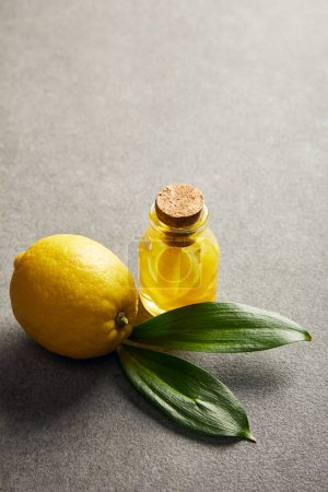 Photo for Whole lemon with green leaves and glass bottle with essential oil on dark surface - Royalty Free Image
