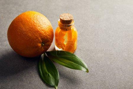 Photo pour Orange entière fraîche avec huile essentielle sur surface foncée - image libre de droit