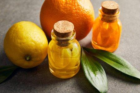 Photo pour Huiles essentielles de citron et d'orange sur la surface sombre - image libre de droit