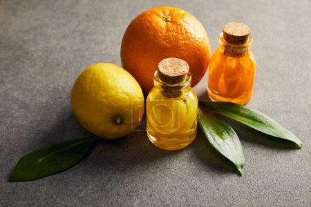 Photo pour Bouteilles d'huile essentielle de citron et d'orange sur la surface sombre - image libre de droit