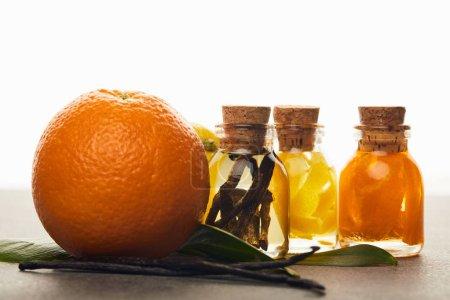 Photo pour Bouteilles d'huile essentielle à l'orange et vanille sur fond blanc - image libre de droit