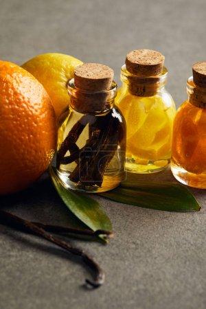 Photo pour Bouteilles d'huile essentielle au citron, à l'orange et à la vanille à la surface sombre - image libre de droit