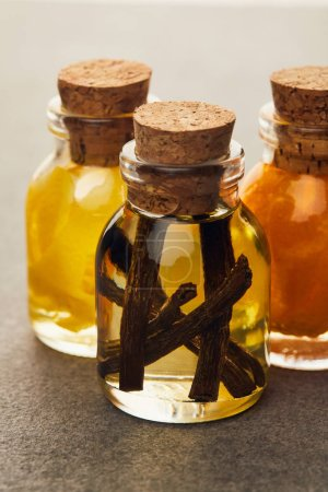Photo pour Bouteilles de verre d'huile essentielle avec fruits vanille et coupées sur la surface sombre - image libre de droit