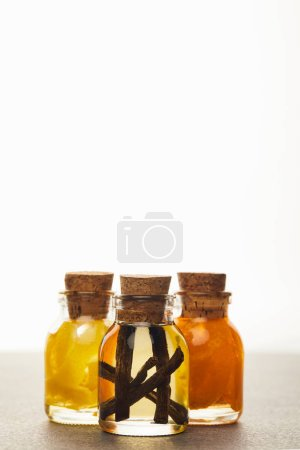Photo pour Bouteilles de verre d'huile essentielle avec les fruits coupés sur fond blanc - image libre de droit