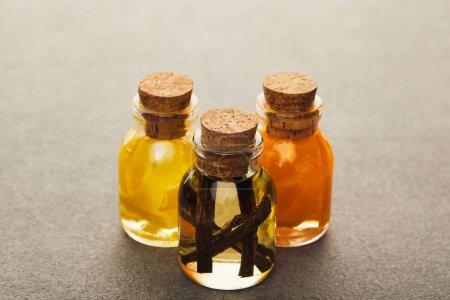 Photo pour Bouteilles de verre d'huile essentielle avec les fruits coupés et épicé sur surface sombre - image libre de droit