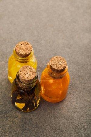 Photo pour Vue de dessus des bouteilles en verre avec des huiles essentielles organiques sur la surface sombre - image libre de droit