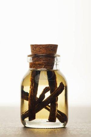 Photo pour Bouteille en verre d'huile essentielle avec des gousses de vanille sur fond blanc - image libre de droit