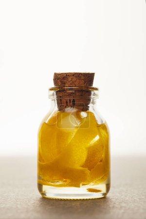 Photo pour Bouteille en verre d'huile essentielle avec les fruits coupés sur fond blanc - image libre de droit