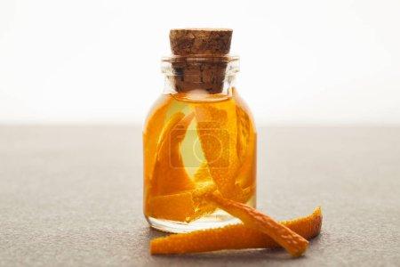 Photo pour Bouteille en verre d'huile essentielle bio avec morceaux d'orange sur fond blanc - image libre de droit
