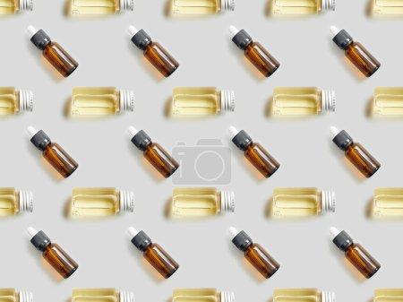 Photo pour Plat poser avec des bouteilles de verre d'huile essentielle sur fond gris - image libre de droit
