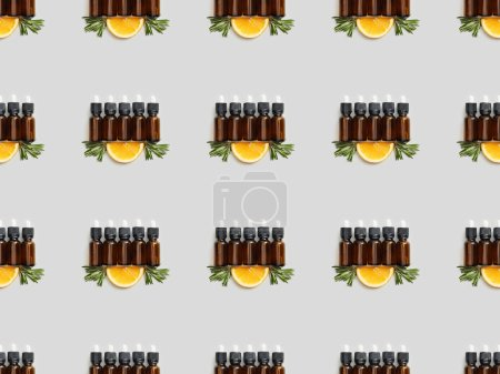 Photo pour Modèle avec des bouteilles en verre d'huiles essentielles et coupe orange sur fond gris - image libre de droit