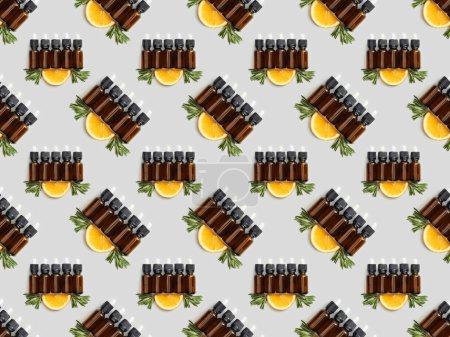 Photo pour Modèle avec bouteilles brunes avec huiles essentielles et de tranches d'orange sur fond gris - image libre de droit
